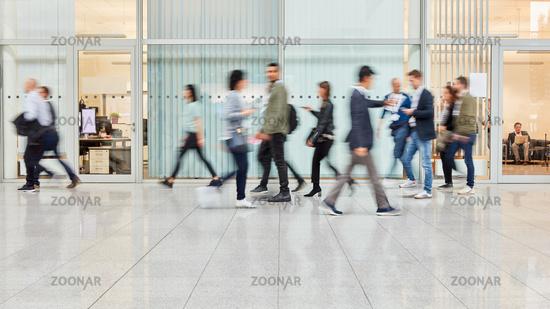 Viele verschwommene Menschen gehen durch Büro