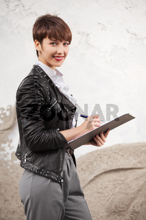 Happy young fashion business woman in leather jacket with clipboard