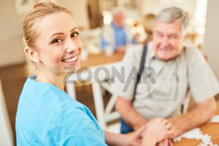 Lächelnde Pflegehilfe tröstet einen Senior