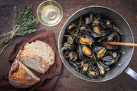 Traditional barbecue Italian blue mussel with farmhouse bread and white wine as top view in a casserole
