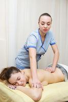 Masseuse makes massage to a nice brunette