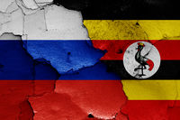 flags of Russia and Uganda painted on cracked wall