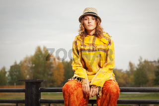 Young fashion hipster woman sitting on handrail outdoor
