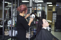 Professional hairdresser preparing to give a haircut to her beautiful cheerful female client combing her hai