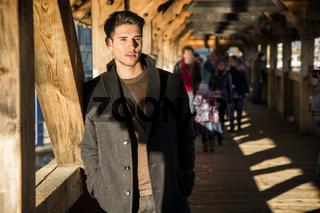Young man standing on wooden footbridge in Switzerland