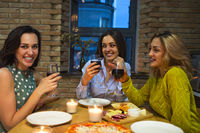 Three female friends toasting with red wine in the kitchen