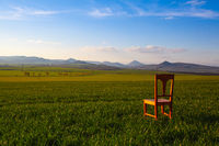 Sunset with old chair in the spring field in Central Bohemian Highlands, Czech Republic.