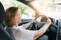 Elderly woman behind the steering wheel of a car