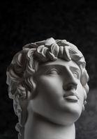 Gypsum copy of ancient statue Antinous head on dark textured background. Plaster sculpture man face.