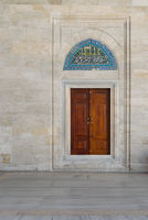 Wooden engraved door on stone wall and tiled marble floor