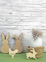 Ostern Hintergrund mit Osterei, Osterhasen und Hahn auf grün vor Holz