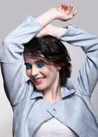Portrait of smiling female in blue jacket with hands up. Woman with unusual beauty makeup and wet hair, and blue shadows make-up.