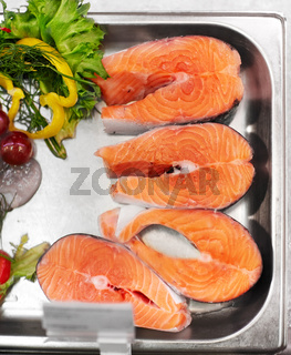 salmon fish fillet in metal tray on ice at grocery
