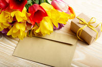 Colorful tulips blank envelope and gift box on natural wooden background with space for text