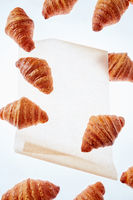 Floating freshly baked croissant on a light background of parchment paper, mock up.