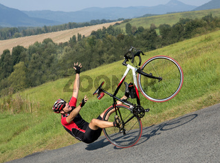 Cyclist falls off the bike on a steep slope.