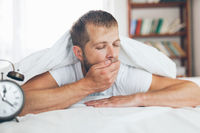 Young man finding it difficult to wake up in the morning