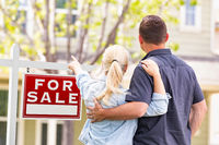 Caucasian Couple Facing and Pointing to Front of For Sale Real Estate Sign and House