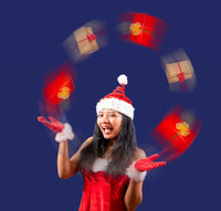 Cheerful Mrs. Claus looks at the camera and juggle with Christmas gifts on blue background.