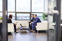 Businessmen interviewing female candidate for job in modern corporate office.