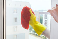hand cleans window glass of urban apartment house