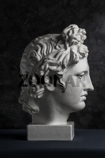Gypsum copy of ancient statue Apollo head on dark textured background. Plaster sculpture man face.