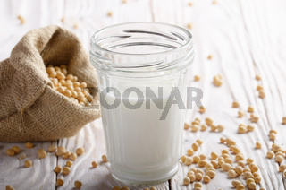 Non-dairy alternative Soy milk or yogurt in mason jar on white wooden table with soybeans in hemp sack