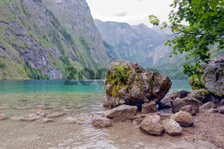 German Konigssee near Berchtesgaden with steep mountains and big rock