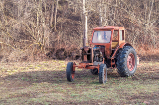 Antique tractor. An old rusty red tractor on a farm in the woods.