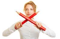 Frau hält zwei gekreuzte große Stifte zur Abwehr