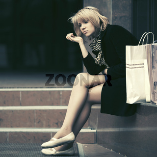 Sad young woman with shopping bags sitting on mall steps