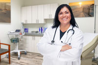 Hispanic Female Doctor Standing In Office