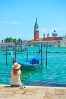 Woman with sunhut at quayside in Venice