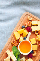 Cheese, honey, berries and nuts on wodden board