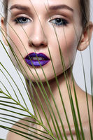 Female portrait with palm branch leaves on foreground and beauty face makeup with violet lips.