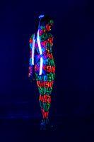 Woman with UV bodyart full-length rearview