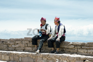 Two men dressed in traditional outfits specific for the Taquile Island region, one of them  knitting a hat. Lake Titicaca, Peru - October 17, 2012
