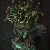 Medusa, creature of Greek mythology. pieces made by hand with goldsmiths and metals such as gold and copper. wears a helmet of green and gold snakes