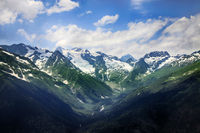 Mountains scene with dramatic blue sky in national park of Dombay