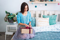 Girl sitting in bed with present box