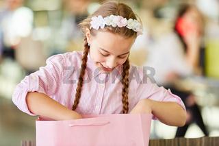 Mädchen schaut neugierig in Einkaufstüte