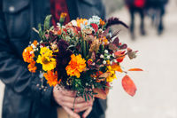 Wedding bouquet in a bright autumn style in the hands of the groom. Marigold flowers