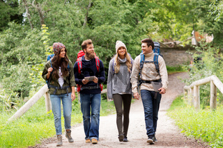 friends or travelers with backpacks and tablet pc