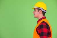 Profile view of happy young multi ethnic man construction worker smiling