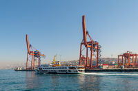 Day shot of the cranes in the shipyard of the Port of Haydarpasha, and passing ferry boat with background view of Istanbul, Turkey