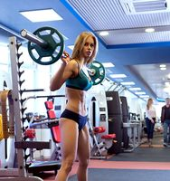 Beautiful girl posing with barbell during workout