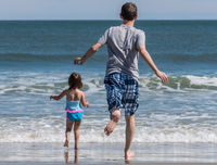 Rear view of father and young daughter running into the ocean waves