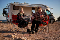 Middle aged travelers couple sitting on folding chairs take break during long trip by recreational vehicle motor home trailer. People in love having romantic date husband play guitar to beloved wife
