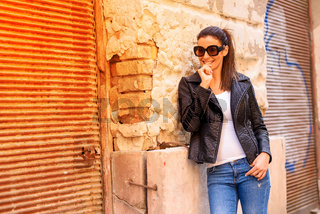 Fashion Portrait of a cheerful young woman in a european urban neighbourhood