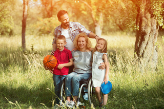 Family portrait. Woman in a wheelchair with her family outdoors.